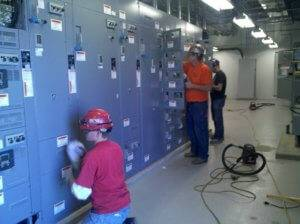 Shaw workers work on multiple electric panels.