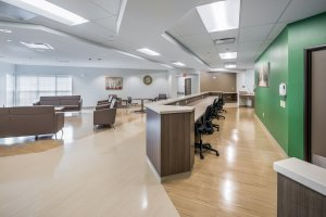 Greeting area and commons at a mental health facility with a green wall.