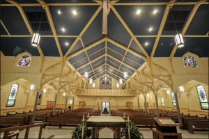 A large sanctuary with traditional stained glass windows and balcony seating in the back.
