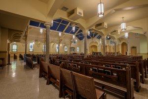 A large catholic sanctuary with pews.