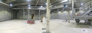 A photo of a large mostly empty cement room.