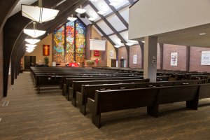 A sanctuary with stained glass and pews.