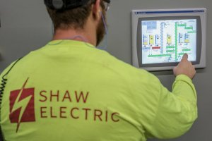 A Shaw employee operates an agricultural system interface.