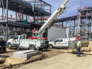 A Shaw Electric crew operates a crane at a job site.